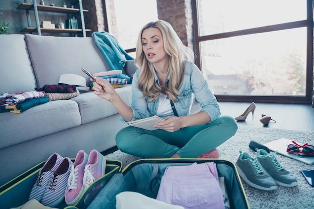Портрет довольно сосредоточенной женщины, проверяющей организацию гардеробной одежды в помещении