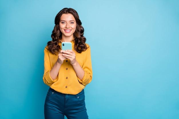 새로운 긍정적 인 의견을 읽고 전화 손을 잡고 예쁜 프리랜서 아가씨의 초상화 인스 타 그램 블로그 게시물 착용 노란색 셔츠 바지.
