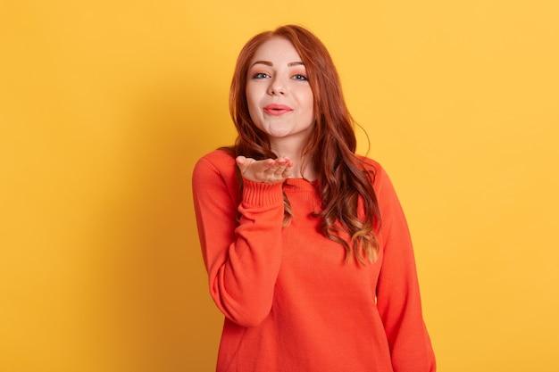 Портрет довольно дружелюбной девушки в повседневном оранжевом джемпере