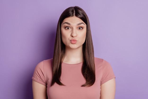 Портрет красивой девушки дует воздушный поцелуй с надутыми губами в камеру, изолированную на фиолетовом цветном фоне