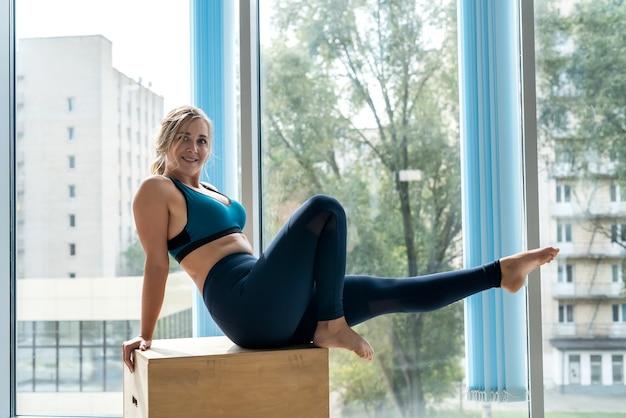 Портрет красивой девушки, сидящей и отдыхающей на деревянном кубе после тренировки в тренажерном зале