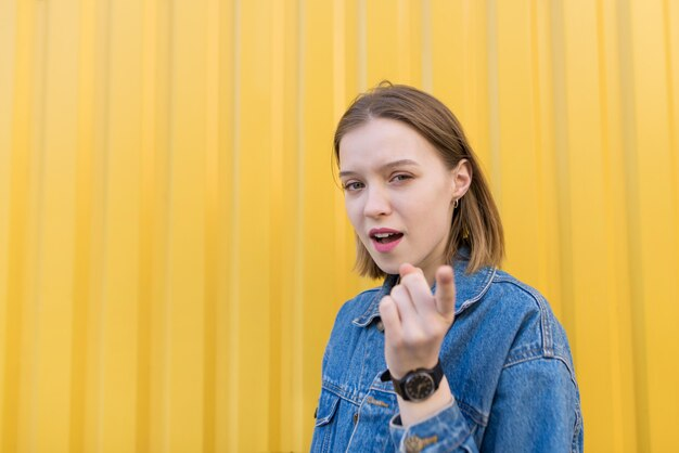 疑わしい表情で黄色の壁の背景に立っているかわいい女の子の肖像画