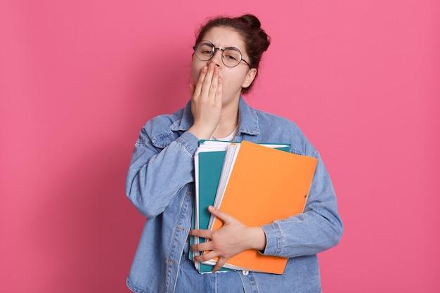 Портрет красивой девушки с булочкой в джинсовой куртке и белой футболке с нежной улыбкой на розовом, прикрывая рот ладонью, зевая.