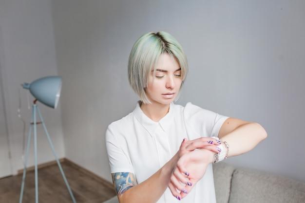 灰色のスタジオに立っている灰色の短い髪型でかわいい女の子の肖像画。彼女は白いドレスと軽い化粧を着ています。彼女は時計を見ています。