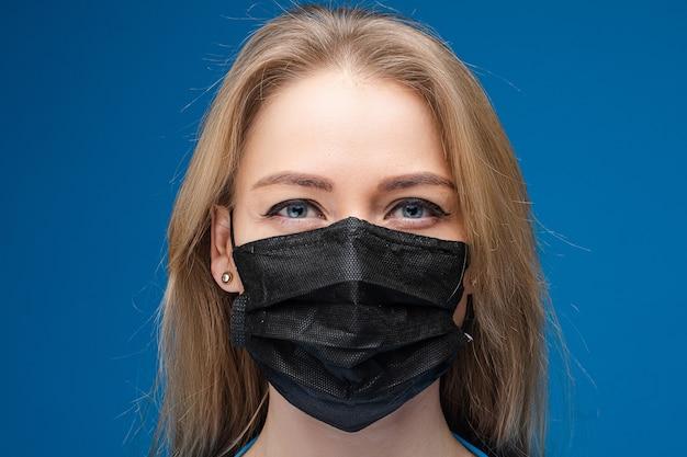 그녀의 얼굴에 의료 마스크와 긴 공정한 머리를 가진 예쁜 여자의 초상화