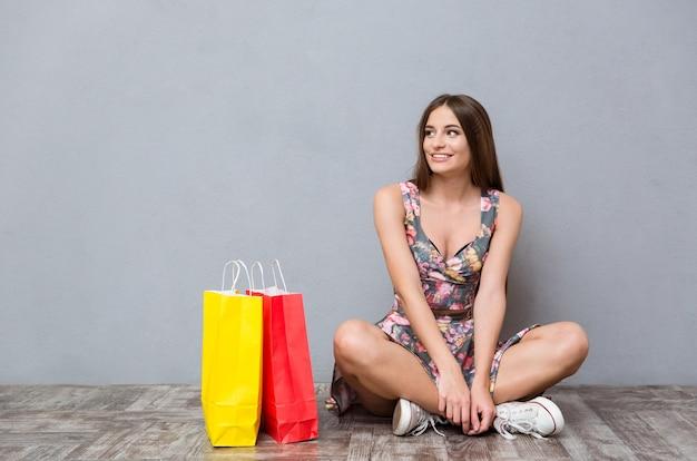 Портрет довольно счастливой улыбающейся кавказской девушки, сидящей на полу возле разноцветных подарков со скрещенными ногами, глядя в сторону