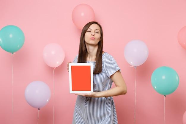 青いドレスを着たかなり幸せな女性の肖像画は、カラフルな空気の風船でパステルピンクの背景にキスする唇を吹く空白の空の画面でタブレットpcコンピューターを保持します。誕生日の休日のパーティーのコンセプト。