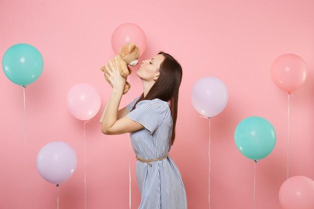 파란색 드레스를 입고 분홍색 배경에 화려한 공기 풍선이 달린 테디 베어 봉제 장난감을 들고 키스하는 꽤 행복한 젊은 여성의 초상화. 생일 휴가 파티, 사람들은 진심 어린 감정 개념입니다.
