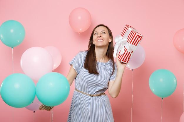 明るいトレンドのピンクの背景にギフトプレゼントとカラフルな気球と赤い箱を持って見上げることを夢見ている青いドレスを着てかなりうれしそうな女性の肖像画。誕生日の休日のパーティーのコンセプト。