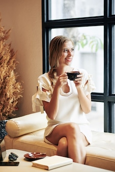 Портрет довольно радостной молодой женщины, пьющей чашку вкусного кофе и смотрящей в окно