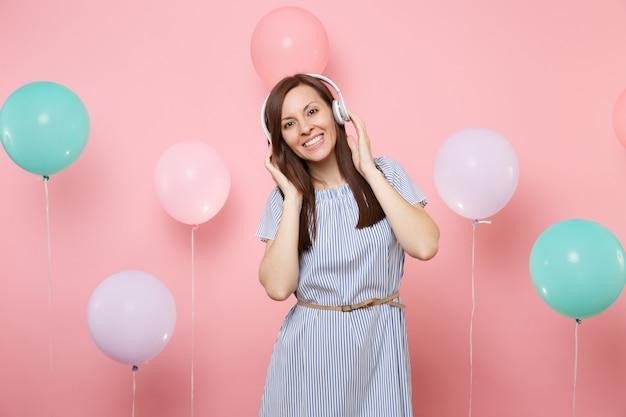 カラフルな気球とパステルピンクの背景に頭の近くに手を置いて音楽を聴いて青いドレスを着てヘッドフォンでかなりうれしそうな若い女性の肖像画。誕生日の休日のパーティーのコンセプト。