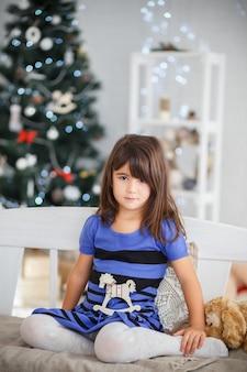 Портрет красивой маленькой девочки в синем полосатом платье, сидящей на белой скамейке в новогоднем интерьере