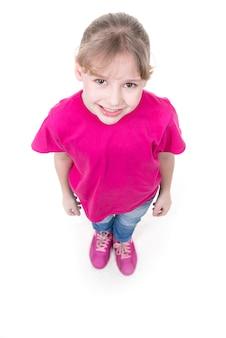 ピンクのtシャツで見上げるかわいい女の子の肖像画。上面図。白い背景で隔離。
