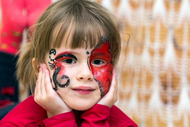 그녀의 얼굴에 나비 그림을 가진 예쁜 소녀의 초상화