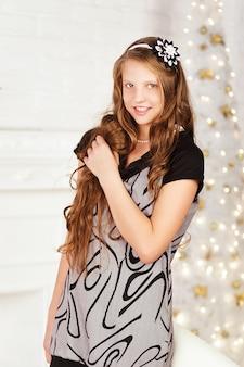 Портрет довольно длинноволосой улыбающейся девочки-подростка в платье в интерьере с рождественскими украшениями