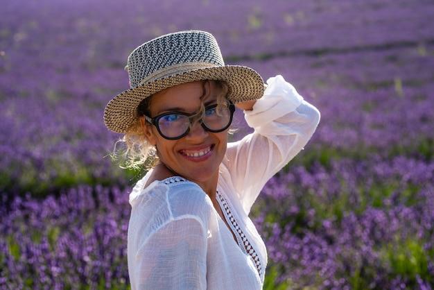 背景に紫紫のラベンダー畑を持つかなり中年の陽気な女性の肖像画-女性はフランスのプロヴァンスでの休日の休暇のために夏のシーズンに旅行して屋外を楽しむ