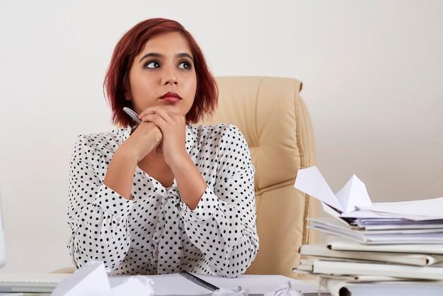 書類の山とr ...とオフィスの机に座っているかなり物思いにふける女性起業家の肖像画
