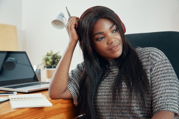 オフィスの机に座っているときにヘッドフォンで音楽を聴いているかなり物思いにふける若い女性の肖像画