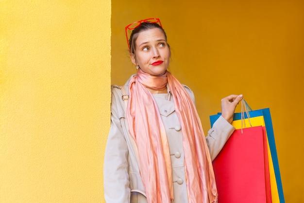 Портрет красивой задумчивой девушки с новой одеждой в пакетах, глядя в сторону и думая