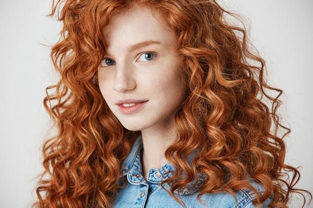Портрет довольно рыжая девушка улыбается.