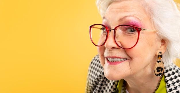 Портрет довольно старшей женщины позирует