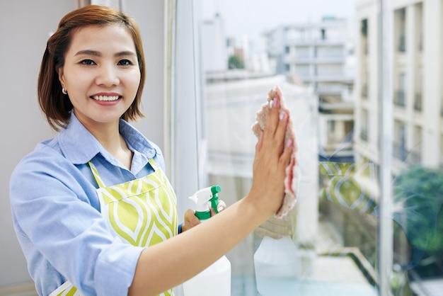 꽤 웃는 아시아 주부의 초상화 아파트 창을 닦아 카메라를보고