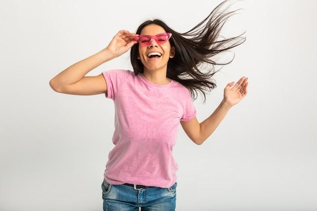 ピンクのシャツとスタイリッシュなサングラス、白い歯、ポジティブなポーズの孤立した、長い髪のかわいい笑顔の感情的な女性の肖像画