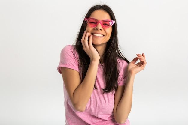 ピンクのシャツとスタイリッシュなサングラス、白い歯、孤立したポジティブなポーズでかなり笑顔の感情的な女性の肖像画