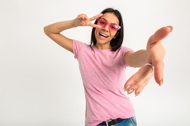 ピンクのシャツとサングラスで彼女の腕を前に保持しているかなり笑顔の感情的な女性の肖像画