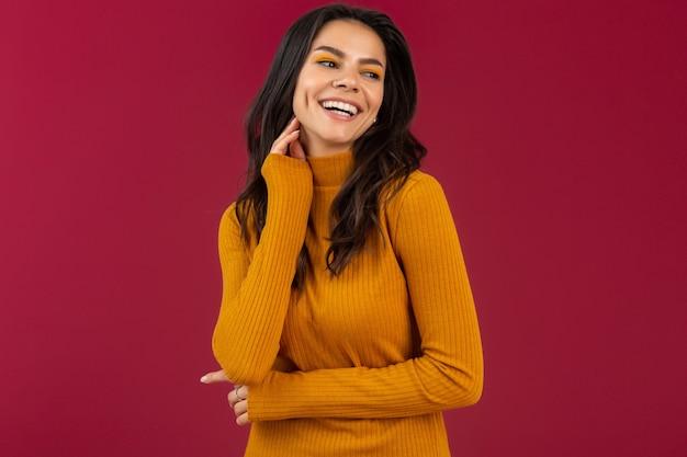 Портрет довольно улыбающейся стильной брюнетки латиноамериканского происхождения в желтом осеннем зимнем модном платье-свитере, позирующей изолированно на красной стене