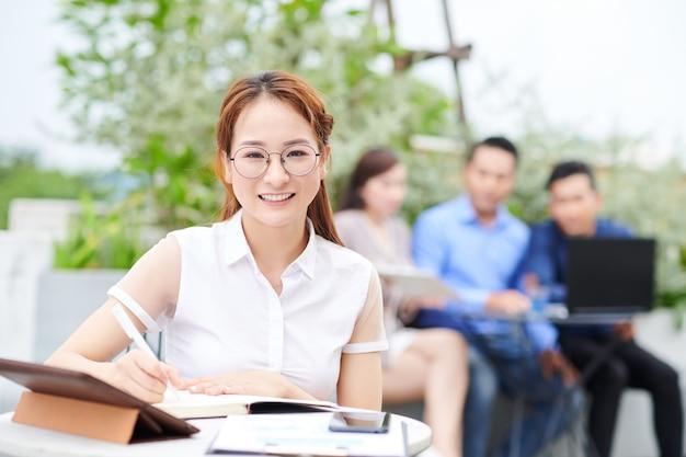 Портрет довольно улыбающейся вьетнамской студентки университета, сидящей за столиком в кафе и работающей над своим исследованием