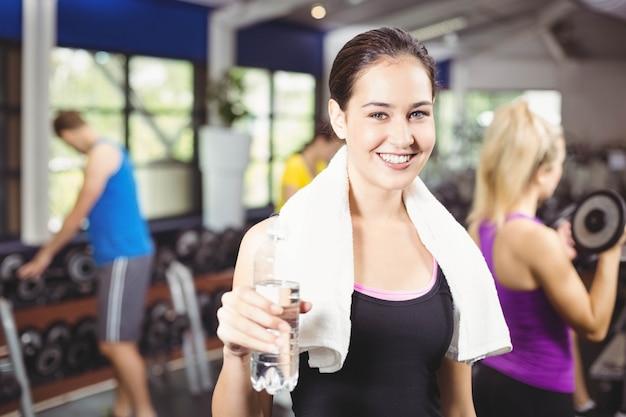 Портрет довольно улыбается женщина с бутылкой воды в тренажерном зале