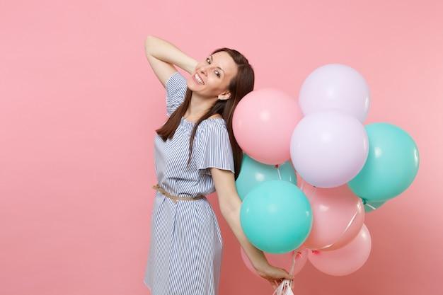 明るいピンクの背景で隔離の頭の近くに手を保持しているカラフルな気球を保持している青いドレスのかわいい笑顔の若い女性の肖像画。誕生日の休日のパーティー、人々の誠実な感情の概念。
