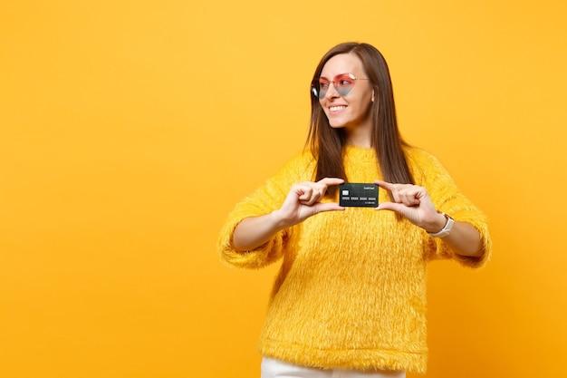 黄色の背景で隔離のクレジットカードを保持し、脇を見て、毛皮のセーター、ハートの眼鏡でかなり笑顔の若い女性の肖像画。人々の誠実な感情、ライフスタイルのコンセプト。広告エリア。