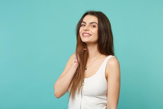 푸른 청록색 배경에 격리된 머리에 손을 얹고 카메라를 찾고 있는 가벼운 캐주얼 옷을 입은 꽤 웃고 있는 젊은 여성의 초상화. 사람들은 진심 어린 감정 라이프 스타일 개념입니다. 복사 공간을 비웃습니다.