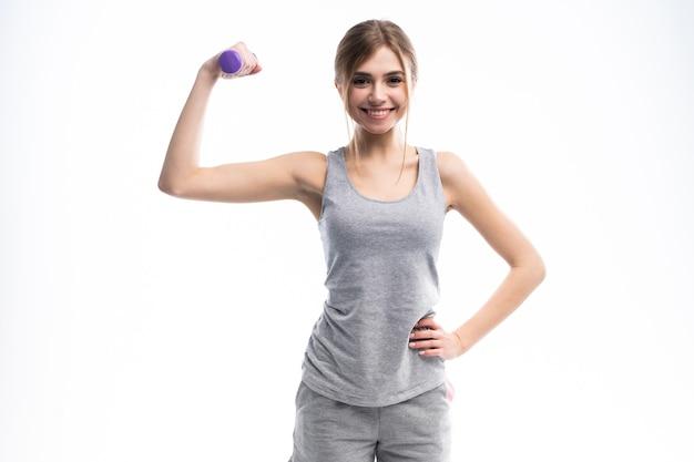 Портрет довольно спортивный девушка держит гантели весов и делает упражнения на белом.