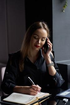 かなりスタイリッシュな若い女性フリーランサーwthラップトップと日記の職場の上に座って、電話で話しているの肖像画。