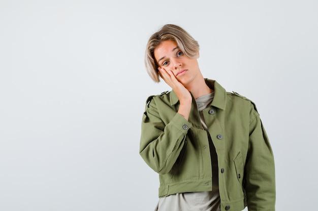緑のジャケットの手のひらに頬を傾けて、陰気な正面図を見てかわいい十代の少年の肖像画