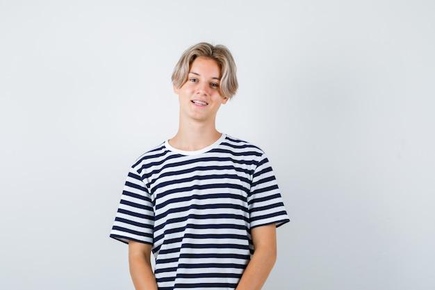 縞模様のtシャツでポーズをとって、陽気な正面図を探しているかわいい十代の少年の肖像画