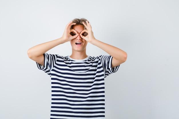 Портрет симпатичного мальчика-подростка, показывающего жест в очках в полосатой футболке и выглядящего удивленным, вид спереди