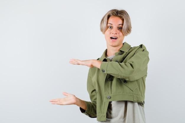 緑のジャケットで大きなサイズのサインを示し、不思議な正面図を見てかわいい十代の少年の肖像画