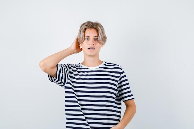 줄무늬 티셔츠를 입고 머리 뒤에 손을 얹고 혼란스러운 앞모습을 보고 있는 예쁜 10대 소년의 초상화