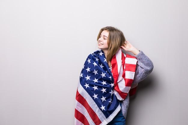Портрет красивой девушки-подростка, держащей флаг сша, изолированный на сером. празднование 4 июля.