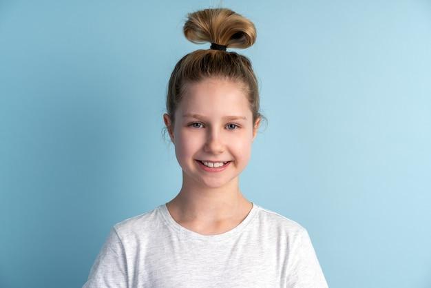 青い壁に立っている白いtシャツのかわいい十代の少女の肖像画