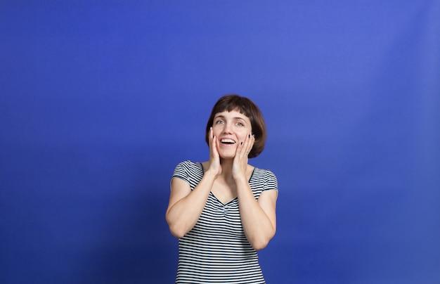 青い背景に縞模様のドレスを着た短い髪のきれいな 30 歳の女性の肖像画