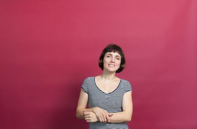 ピンクの背景に縞模様のドレスを着た短い髪のきれいな 30 歳の女性の肖像画
