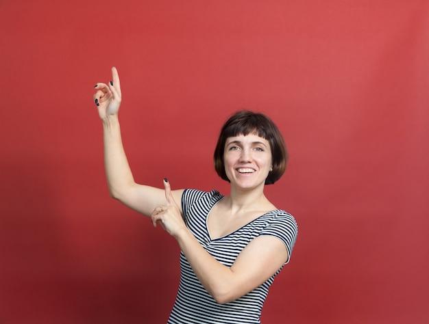 赤い背景に縞模様のドレスを着た短い髪のきれいな 30 歳の女性の肖像画