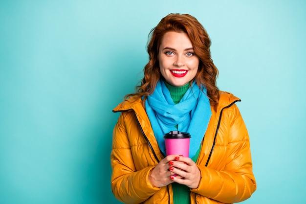 예쁜 여행자 아가씨의 초상화 뜨거운 커피 음료 손을 잡고 해외 자유 시간을 보내고 캐주얼 노란색 외투 스카프 녹색 터틀넥을 착용하십시오.