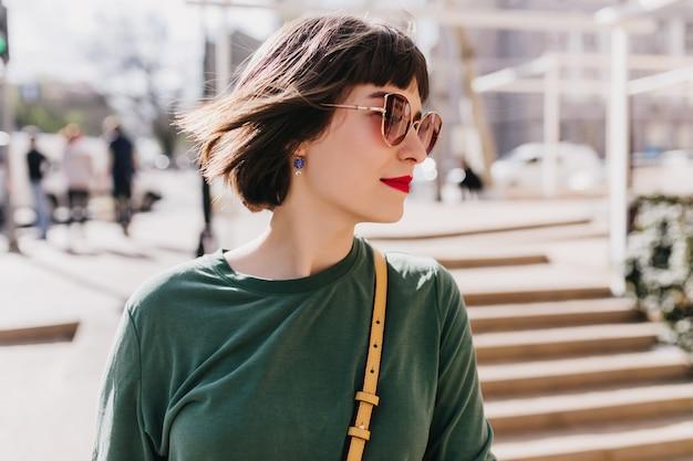 거리를 둘러보고 귀걸이에 예쁜 백인 여자의 초상화. 선글라스에 황홀한 짧은 머리 갈색 머리 여자의 야외 사진.