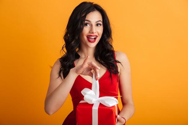 Портрет симпатичной женщины 20-х годов в красном платье с возбужденным взглядом, разворачивающей подарочную коробку на день рождения, изолированную над желтой стеной